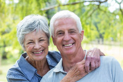 Happy old couple smiling. In a park on a sunny day royalty free stock photo