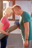 Happy old couple with yoga mats touching foreheads. In fitness class Stock Image