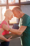 Happy old couple with yoga mats touching foreheads. In fitness class Royalty Free Stock Images