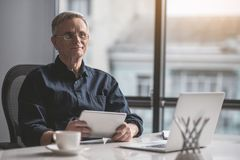 Happy old employer working with gadgets. Portrait of smiling retire male typing in digital device while sitting at table with laptop. Work in office concept Royalty Free Stock Images