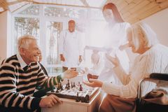 Chess Play. Nursing Home. Elderly. Male. Patient. Happy old family time together. Aged men play with old woman. game with family. Old wife with young nurse stock images
