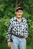 Happy Old Farm Man. Smiling old man posing in front of a tree Royalty Free Stock Image
