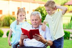 Happy old grandfather reading book for cute children  in garden. Happy old grandfather reading book for his cute grandchildren  in garden Royalty Free Stock Photo