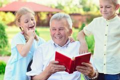 Happy old grandfather reading book for cute children  in garden Stock Photos