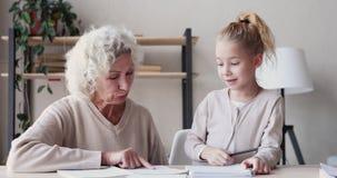 Happy old grandmother helps cute school kid granddaughter with homework