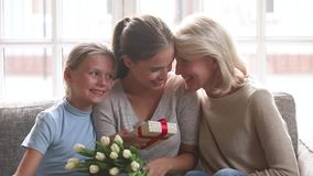 Happy old grandmother and little daughter congratulating young mom stock footage