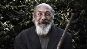 Happy old homeless. Portrait of an elderly bearded men with a smile on face stock photos