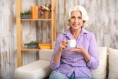Happy old lady drinking hot beverage at home Royalty Free Stock Photo
