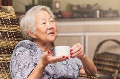 Happy old lady holding a cup of tea. Old lady japanese descendant seated comfortably at home holding a cup of tea with a happy expression of who is having a good Royalty Free Stock Photo