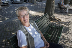 Happy old lady on park bench Royalty Free Stock Photos
