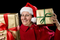 Happy Old Lady in Red with Wrapped Golden Gifts. Cheerful mature female with Santa Claus cap and red coat. Holding a gift to her left cheek and another at an Royalty Free Stock Photo