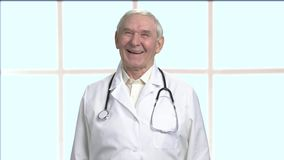 Happy old male doctor in bright room. Checkered framed windows background stock video
