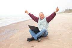 Happy old man on the beach with a laptop. On a foggy day Royalty Free Stock Image