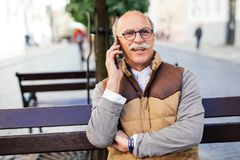 Happy old man calling on smartphone sitting on bench at summer park. Technology, senior people, and communication concept - happy old man calling on smartphone Stock Image