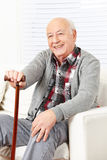 Happy old man with cane. Sitting at home on a sofa royalty free stock images