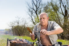 Happy Old Man Checking Grilled Meat with Knife. Happy Old Man with Open Shirt and Sitting on his Wheelchair Checking the Grilled Meat on Stick Using Knife to Royalty Free Stock Photography