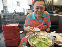 Happy old man eating a shabu shabu (hot pot). In public food center Stock Images