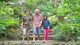 Happy old man with grandchildren walk at park