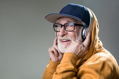 Delighted male person with earphones. Happy old man with grin from ear to ear. He is wearing headphones over the cap. Copy space in left side. on grey background stock photos
