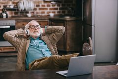 Happy old man in headphones using laptop with feet. On table royalty free stock photo