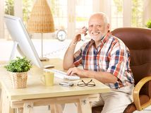 Happy old man on landline call. Sitting at desk using, computer, smiling, looking at camera Stock Images
