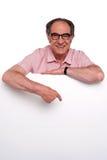 Happy old man pointing at blank billboard Royalty Free Stock Photos