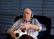 Old man with soccer ball watching tv. Happy old man with remote control and soccer ball sitting in armchair at home and watching football match on tv Royalty Free Stock Photography