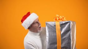 Happy old man in santa hat carrying huge giftbox, holiday sale, big discounts. Stock footage stock footage