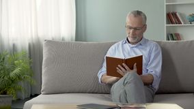 Happy old man sitting on couch and reading interesting book, hobby and free time