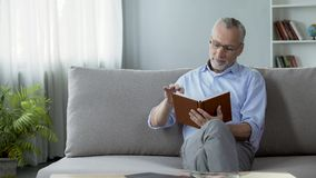 Happy old man sitting on couch and reading weekend plan, hobby and free time. Stock footage Royalty Free Stock Images