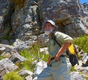 Happy old man stands in front of rock. Shot in Table Mountain (cable car area), Cape Town, South Africa Royalty Free Stock Image