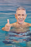 Happy old man in swimming pool. Holding his thumbs up Stock Images