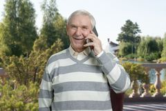 Happy old man talking on phone outdoor. Cheerful senir with gadget. Summer park background Stock Photo