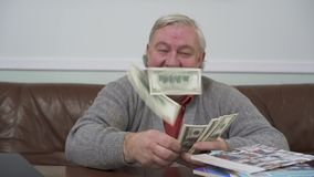 Happy old man throwing away the dollars sitting at the wooden table close up. Positive rich man demonstrates his money