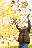 Happy old man throwing leaves around. In parkland Royalty Free Stock Photos