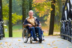 Happy old man on wheelchair in the park. Happy old man on wheelchair in the colorful autumnal park - outdoor scene Stock Photography