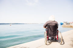 Happy Old Man In Wheelchair. Looking at the sea Stock Photography