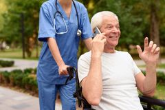 Happy old man in a wheelchair talking on a mobile phone Stock Image
