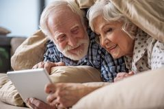 Calm pensioners surfing the internet at home royalty free stock photography