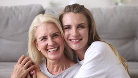 Happy old mother embracing young adult woman laughing together. Happy old mature mother embracing young adult woman looking at camera laughing together, smiling stock footage
