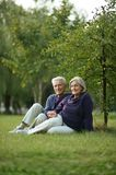 Happy old people. Beautiful happy old people sitting in the autumn park Stock Photography