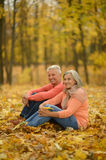 Happy old people. Beautiful happy old people sitting in the autumn park Stock Photos