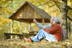Happy old people. Beautiful happy old people sitting in the autumn park Royalty Free Stock Photo