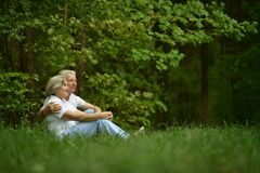 Happy old people. Beautiful happy old people sitting in forest Stock Photos