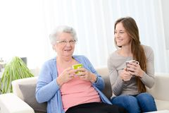 Happy old senior woman spending time and drinking tea with a cheerful young girl at home stock images