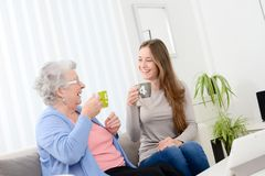 Happy old senior woman spending time and drinking tea with a cheerful young girl at home. Happy old senior women spending time and drinking tea with cheerful Royalty Free Stock Image