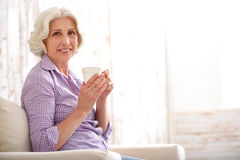Happy old woman drinking beverage at home Royalty Free Stock Images