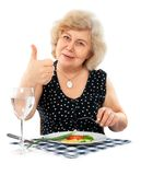 Happy old woman eating healthy food. Isolated on white background stock image