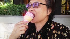 Happy old woman eating strawberry ice cream at park stock video footage