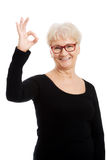 Happy old woman in eye glasses showing OK. Royalty Free Stock Photos
